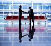 Affärsmän som talar affär i flygplatsen fotografering för bildbyråer