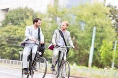 Affärsmän som talar, medan cykla utomhus arkivbilder