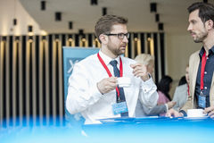 Affärsmän som talar under kaffeavbrott på lobbyen av konventcentret Royaltyfria Foton