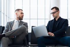 Affärsmän som tillsammans arbetar på bärbara datorn i flygplatsvardagsrum arkivbild
