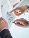 Affärsmän som undersöker en finansiell rapport Arkivbild