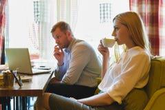 Affärsmöte i ett kafé Kvinnan dricker kaffe, och mannen ser bärbara datorn Royaltyfri Bild