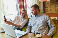 Affärsmöte i ett kafé Man och kvinna som ser minnestavlaPC arkivbilder