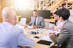 Affärsmöte mellan fyra yrkesmässiga företagsamma ledare inomhus arkivbild