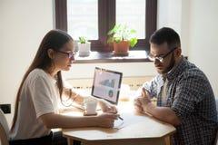 Affärsmöte: två millennial coworkers som löser funktionsdugligt sökande royaltyfria bilder