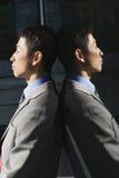 Affärsman Against Reflective Wall med stängda ögon Arkivfoto