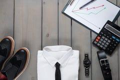 Affärsman arbetsdräkt på grå träbakgrund Vit skjorta med smokingen, klocka, bälte, oxford skor, planchette Royaltyfria Foton