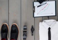 Affärsman arbetsdräkt på grå träbakgrund Vit skjorta med smokingen, klocka, bälte, oxford skor, planchette Arkivbild