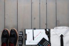 Affärsman arbetsdräkt på grå träbakgrund Vit skjorta med smokingen, klocka, bälte, oxford skor, planchette Arkivfoton