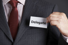 Affärsman Attaching Delegate Badge som klår upp royaltyfri bild