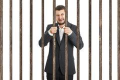 Affärsman bak fängelsecellen arkivbilder