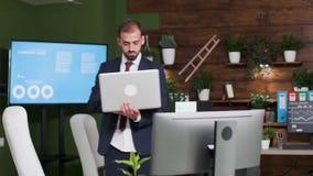 Affärsman bara i kontoret som rymmer en bärbar dator i händer lager videofilmer