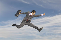 Affärsman With Briefcase Running mot molnig himmel Royaltyfri Bild