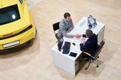 Affärsman Buying Car i visningslokal arkivbild