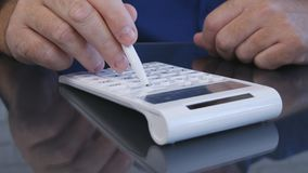 Affärsman Calculates Using en penna och en tillfoga maskin arkivfoton