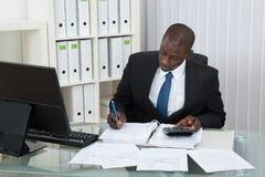 Affärsman Calculating Finance Bills Royaltyfria Foton