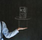 Bemanna att dra pengar från magisk hattblackboardbakgrund Arkivfoto