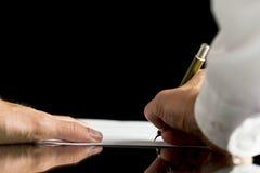 Affärsman eller advokat som undertecknar ett dokument, ett avtal eller ett lagligt Arkivfoto