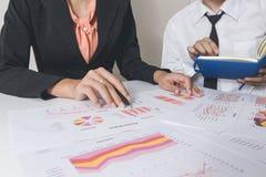 Affärsman eller lag som diskuterar diagrammen och graferna som visar resultaten av deras lyckade teamwork Finansiella rapporter ä Arkivbild
