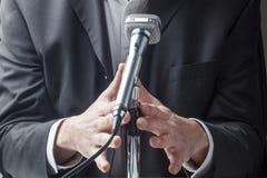 Affärsman eller politiker som talar upp på mikrofonen Arkivfoto
