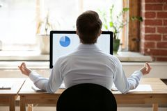 Affärsman för bakre sikt som sitter på skrivbordet mitt emot PC:n som gör yoga royaltyfri foto