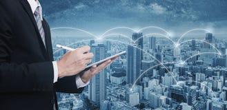 Affärsman för dubbel exponering som använder den digitala minnestavlan och cityscape Affärsnätverk, blockchainteknologi och inter arkivfoto