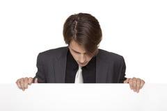 Affärsman - för lookind blankt tecken ner fotografering för bildbyråer