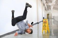 Affärsman Falling på vått golv royaltyfri bild