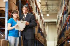 Affärsman And Female Worker i fördelningslager Arkivbild