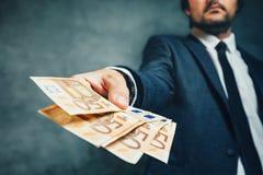 Affärsman från erbjudande pengarlån för bank i eurosedlar Arkivbild