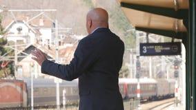 Affärsman Gestures och samtal till mobiltelefonen i en drevstation arkivbilder