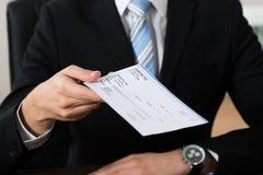 Affärsman Giving Cheque royaltyfri bild