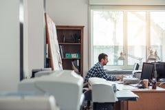 Affärsman hårt på arbete på en bärbar dator i ett kontor royaltyfria foton