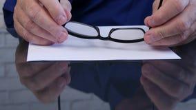 Affärsman Hands Taking Eyeglasses från tabellen som läser ett dokument arkivfilmer