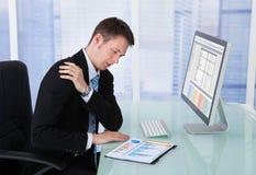 Affärsman Having Shoulder Pain på datorskrivbordet Royaltyfria Bilder