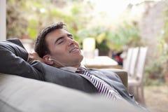 Affärsman hemmastadda With Earphones Relaxing royaltyfri foto
