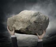 Affärsman Hold en sten Arkivbild
