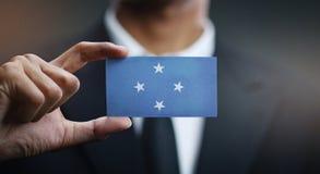 Affärsman Holding Card av den Federated States of Micronesia flaggan royaltyfri bild