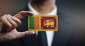 Affärsman Holding Card av den Sri Lanka flaggan arkivfoton