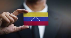 Affärsman Holding Card av den Venezuela flaggan royaltyfria foton