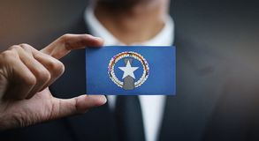 Affärsman Holding Card Northern Mariana Islands Flag royaltyfri bild