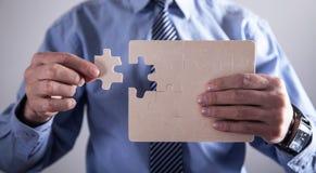 Affärsman Holding Jigsaw Puzzle framgång och affär royaltyfria foton