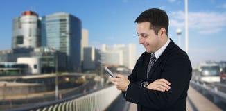 Affärsman Holding Phone While le och känsla som är lyckliga med affärsstaden och företags byggnader i bakgrund royaltyfri fotografi