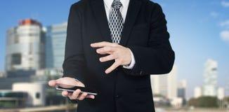 Affärsman Holding Smartphone i hand med handgest över telefonskärmen med affärsstaden och företags byggnader in arkivfoto