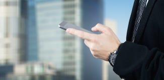 Affärsman Holding Smartphone, i hand och att skriva ett meddelande med affärsstaden och företags, byggnader i bakgrund royaltyfri fotografi