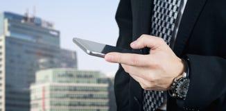 Affärsman Holding Smartphone, i hand och att skriva ett meddelande med affärsstaden och företags, byggnader i bakgrund arkivbild