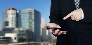 Affärsman Holding Smartphone i hand och pekapekfinger på telefonskärmen med affärsstaden och företags byggnader fotografering för bildbyråer