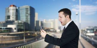 Affärsman Holding Smartphone i handen och känsla som är ilskna med affärsstaden och företags byggnader i bakgrund royaltyfria foton