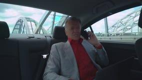 Affärsman i år som rymmer bärbara datorn och använder mobiltelefonsammanträde på backseaten i bilen arkivfilmer