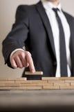 Affärsman i affärsdräkt som förlägger träkvarter på tabellen Royaltyfria Bilder